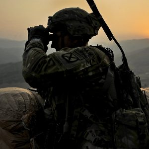 soldier on top of a mountain using binoculars
